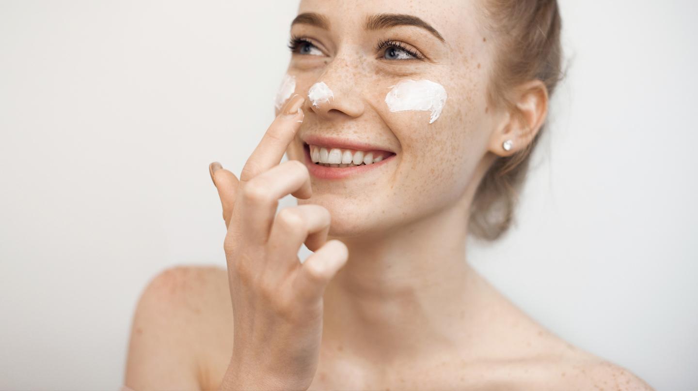 Hautpflege im Frühling: Junge Frau tupft sich Creme auf Wangen und Nase.