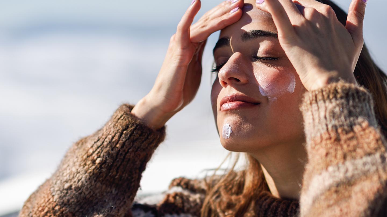 Frühlingssonne: Junge Frau mit Wollpullihält ihr Gesicht in die Sonne und cremt es mit Sonnenschutzmittel ein.